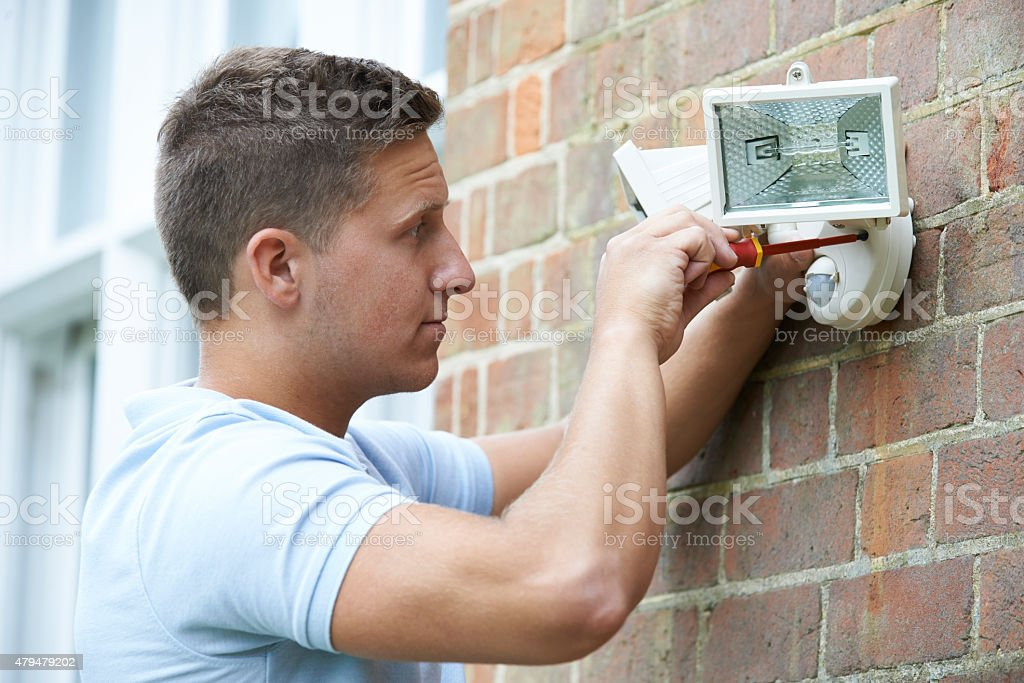 Security Consultant Fitting Security Light To House Wall stock photo
