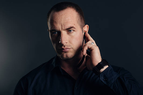 Security detail, bodyguard holding earpiece. Studio shot. stock photo