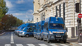 Paris, France - October 15, 2020. View of the security system of the police on the quai des orphévres in Paris along the courthouse where the trial of the Islamist attacks of the satirical newspaper Charlie Hebdo committed in 2015 is taking place. foreground, many vans of the national gendarmerie are parked. In the background, the walls of the courthouse are visible.