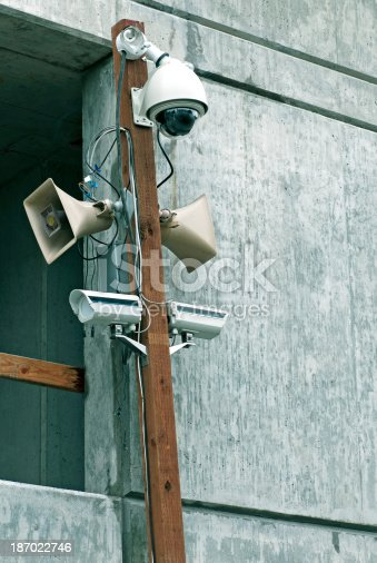 Security devices on wooden pole near concrete wall of apartment building under construction at north edge of downtown Seattle WA