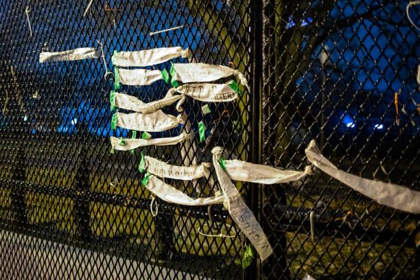 забор безопасности окружает здание белого дома после беспорядков на капитолийском холме со списком виктумов на стене - biden стоковые фото и изображения