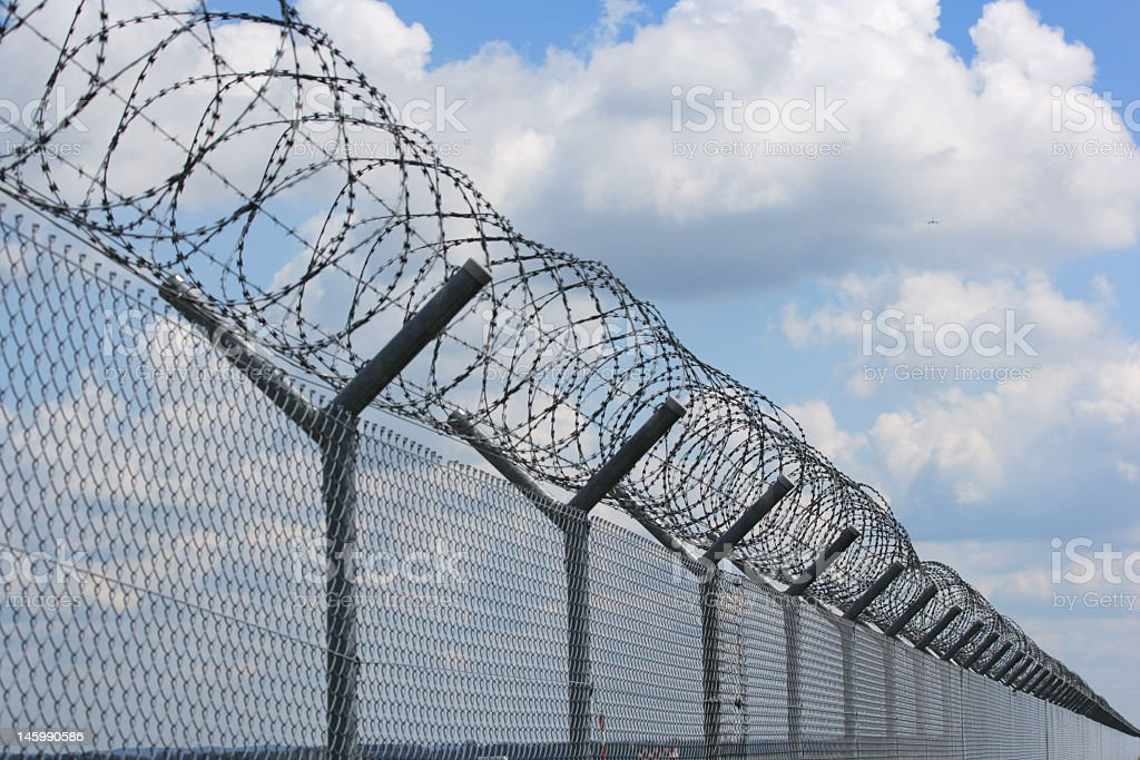 security fence with barbed wire against cloudy sky stock photo