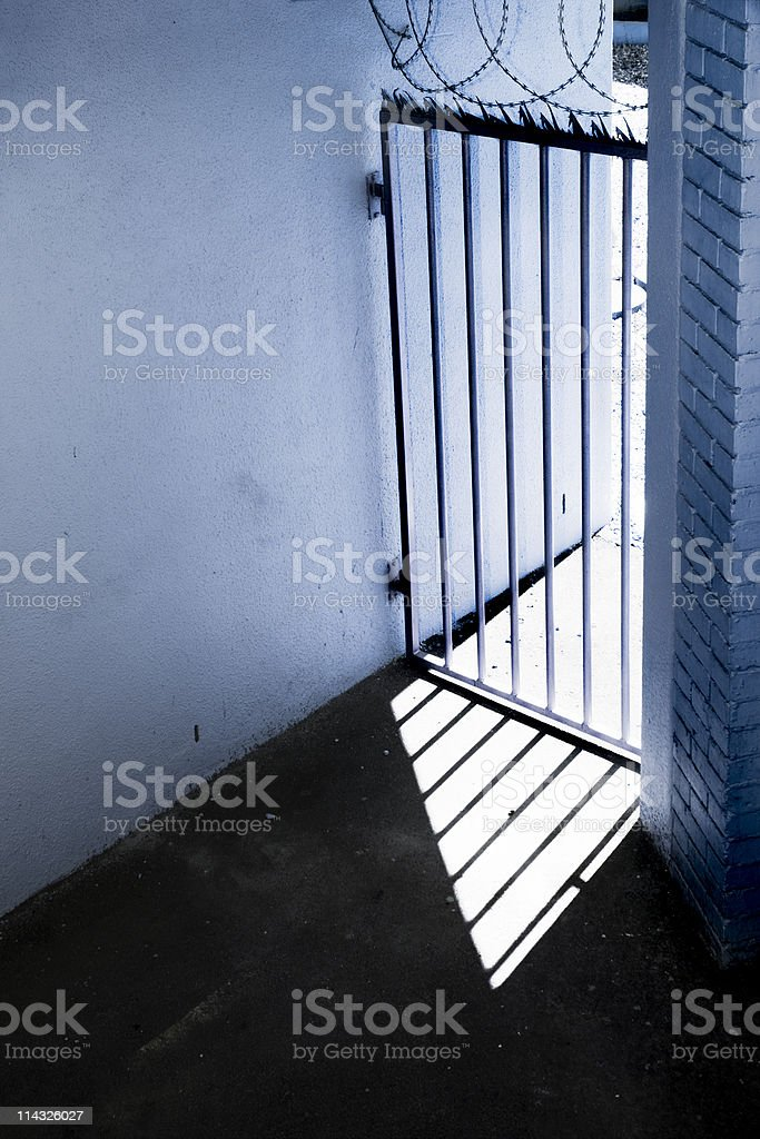 Security gate topped with razor wire for protection stock photo