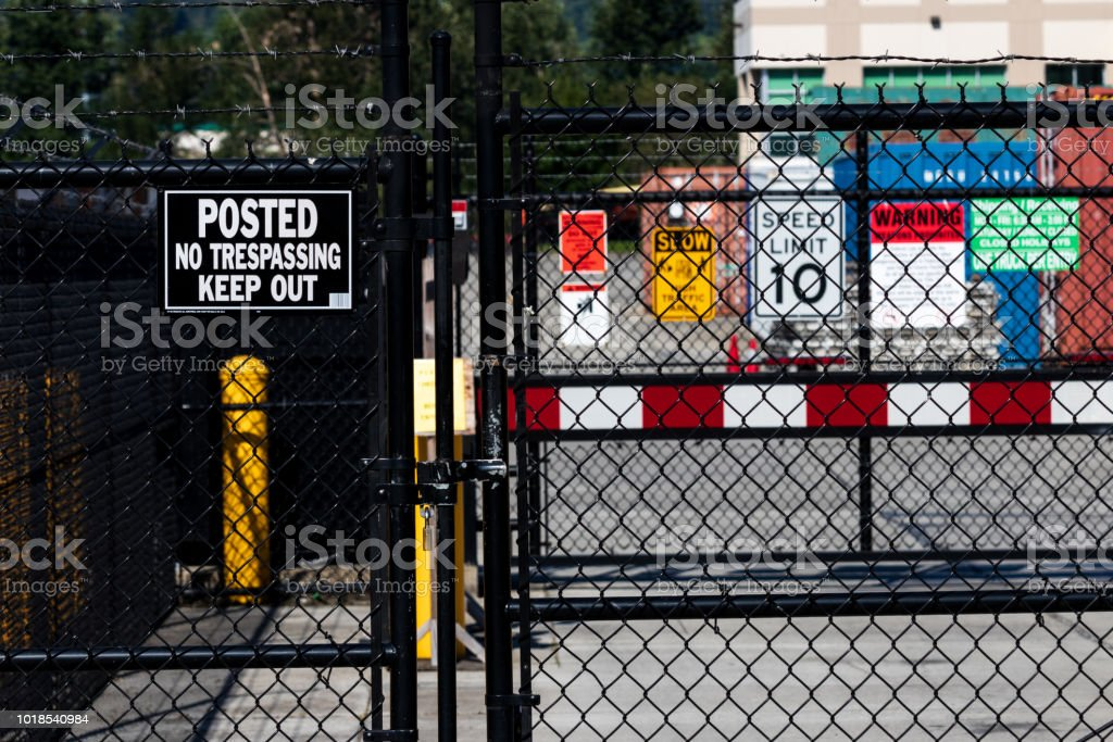 Security gate with various caution and admittance signs stock photo