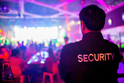 Security guard  are regulating the situation of safety in an event concert in a nightclub.
