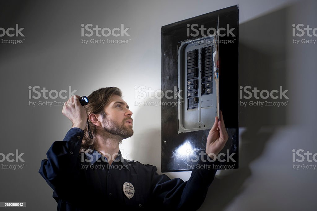 Security guard checking circuit breakers stock photo