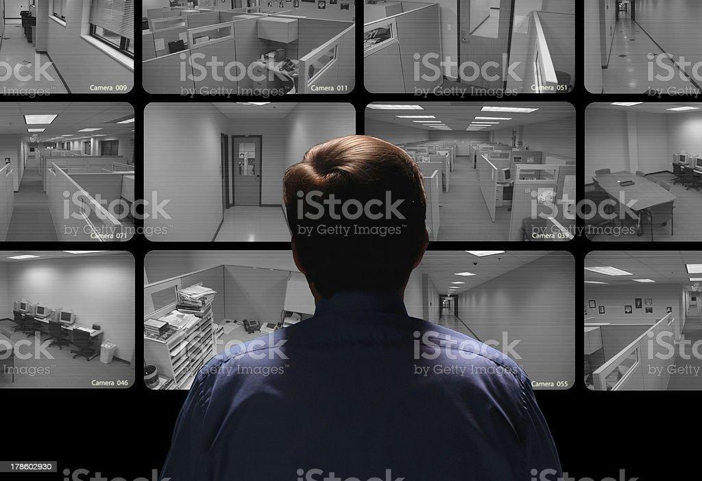Security guard conducting surveillance by watching several monitors royalty-free stock photo