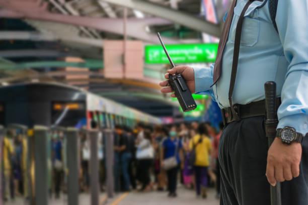 sicherheitswacht kontrolliert indoor-eingangsbahnhof, menschen stehen in linien, die auf bts-himmelszug am bahnhof siam in stoßzeiten warten - hochbahn passagierzug stock-fotos und bilder