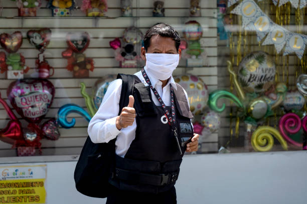 Security guard giving a thumb up wearing a mask amid coronavirus Lima, Peru - April 4 2020: Security guard giving a thumb up wearing a mask amid coronavirus outbreak in south America. amid stock pictures, royalty-free photos & images