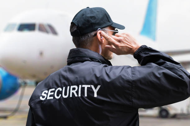 Security Guard Listening To Earpiece Against Building Rear view of mature security guard listening to earpiece against building security staff stock pictures, royalty-free photos & images