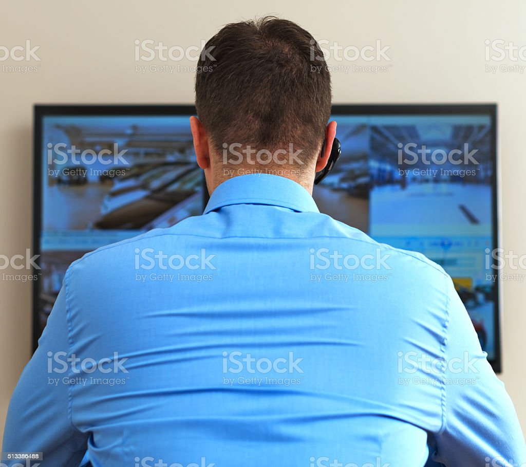 Security guard monitoring video in security room. From the back. stock photo