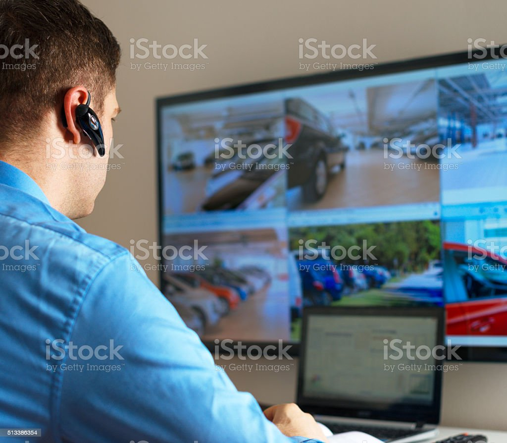 Security guard monitoring video in security room. stock photo