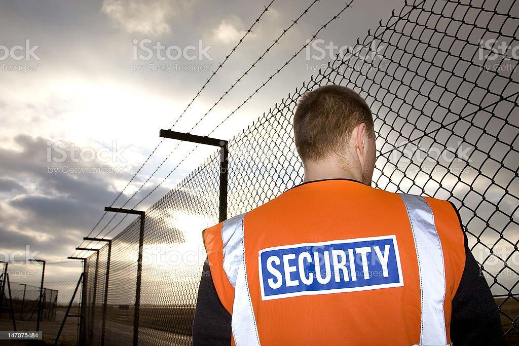 Security guard on patrol near tall fence stock photo