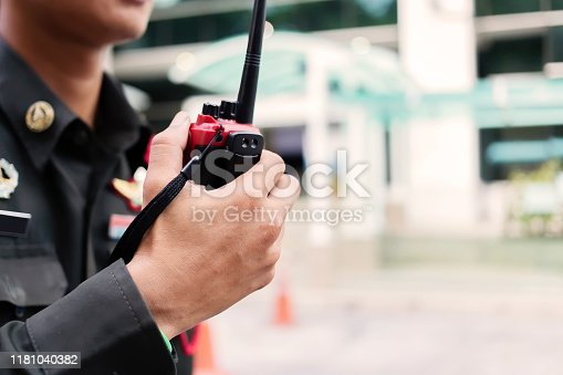 Security guard uses radio communication for facilitate traffic. Traffic Officers use walkie talkie to maintain order in the parking lot in Thailand.