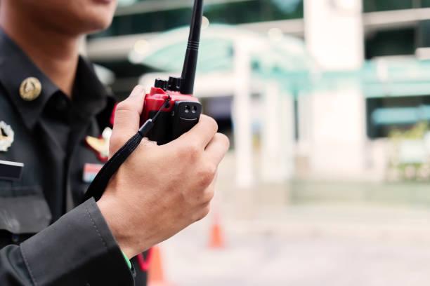 el guardia de seguridad utiliza la comunicación por radio para facilitar el tráfico. los oficiales de tráfico usan walkie talkie para mantener el orden en el estacionamiento en tailandia. - seguridad fotografías e imágenes de stock