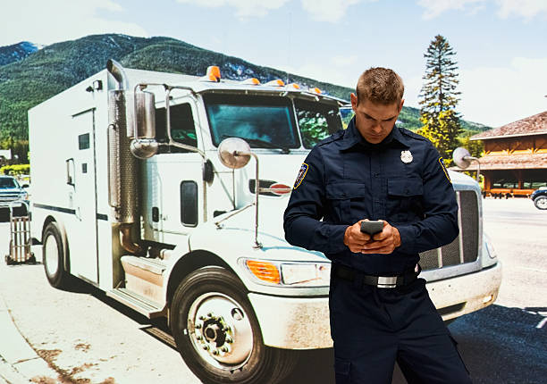 Security guard using phone outdoors stock photo