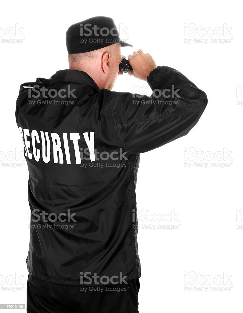 Security guard watching through binoculars rear view stock photo