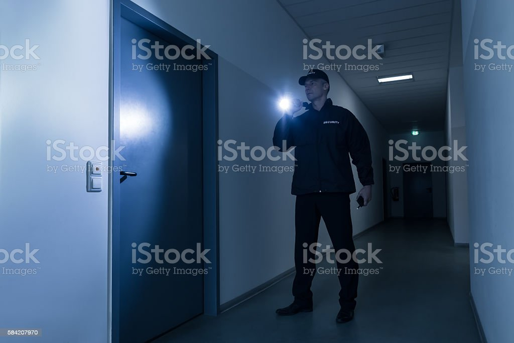 Security Guard With Flashlight Standing In Front Of Door stock photo