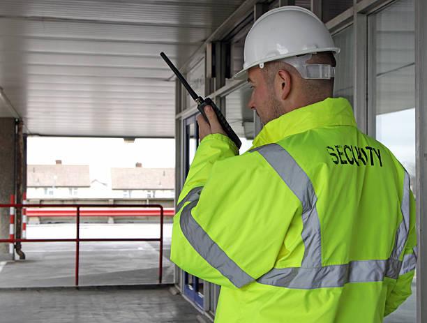 security man talking into a walkie talkie stock photo