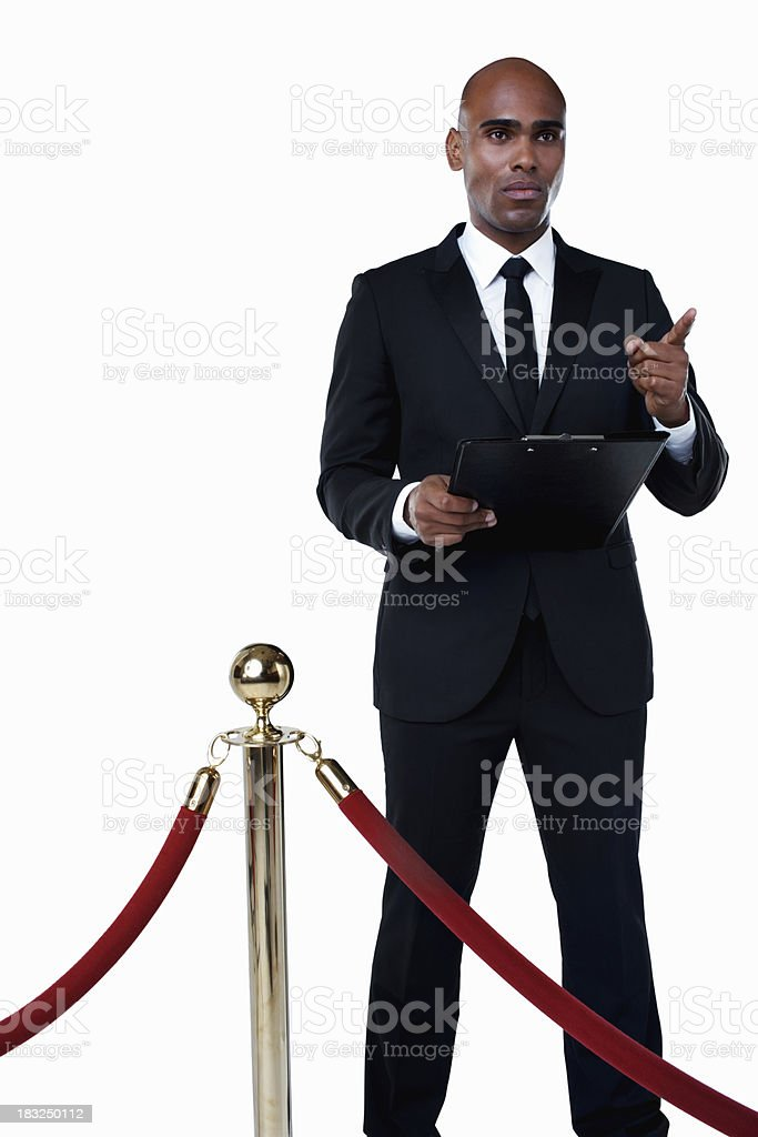Security man with clipboard standing behind crowd control post stock photo
