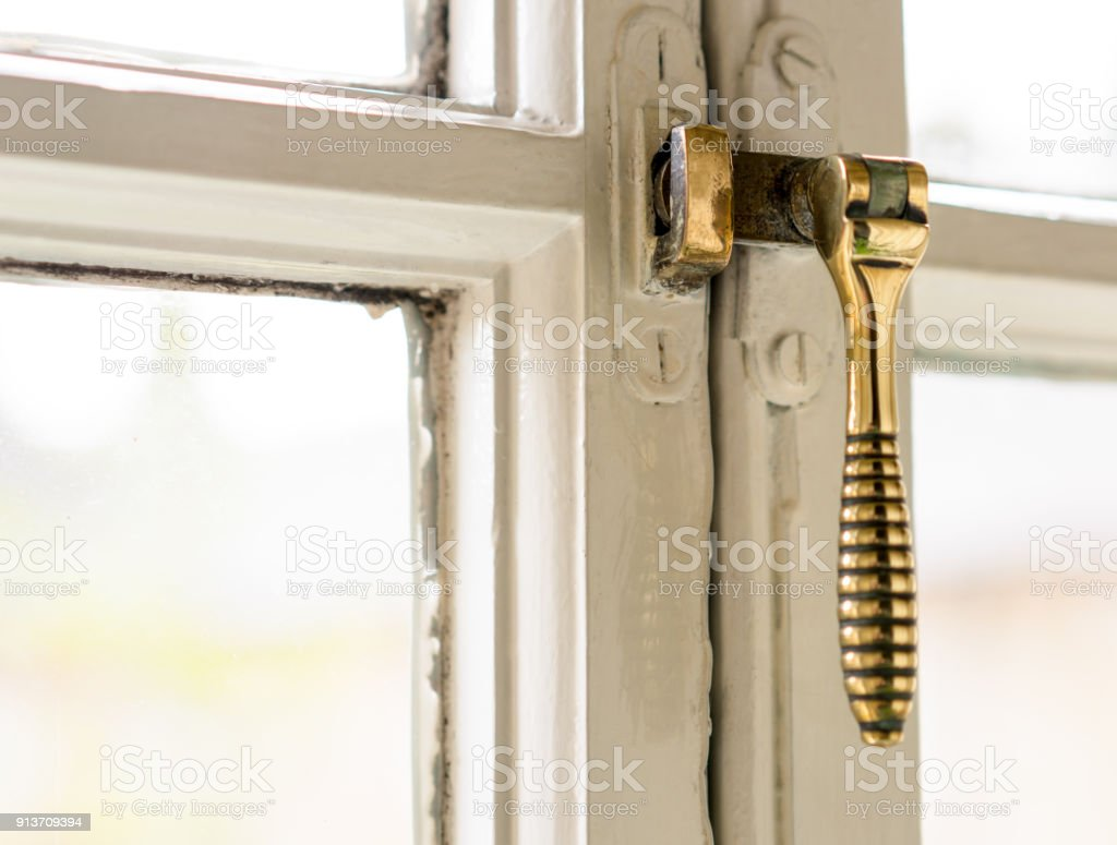 Security: Old fashioned brass window latch stock photo