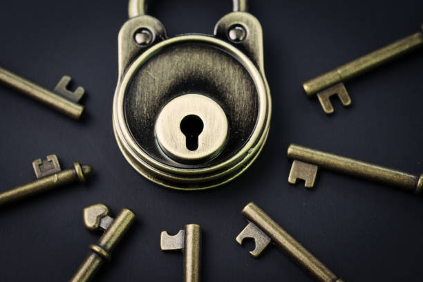 Security or secret protection concept, vintage brass padlock surrounded by multiple keys on a dark black background, internet hacker or cyber safety metaphor Security or secret protection concept, vintage brass padlock surrounded by multiple keys on a dark black background, internet hacker or cyber safety metaphor. surrounding stock pictures, royalty-free photos & images