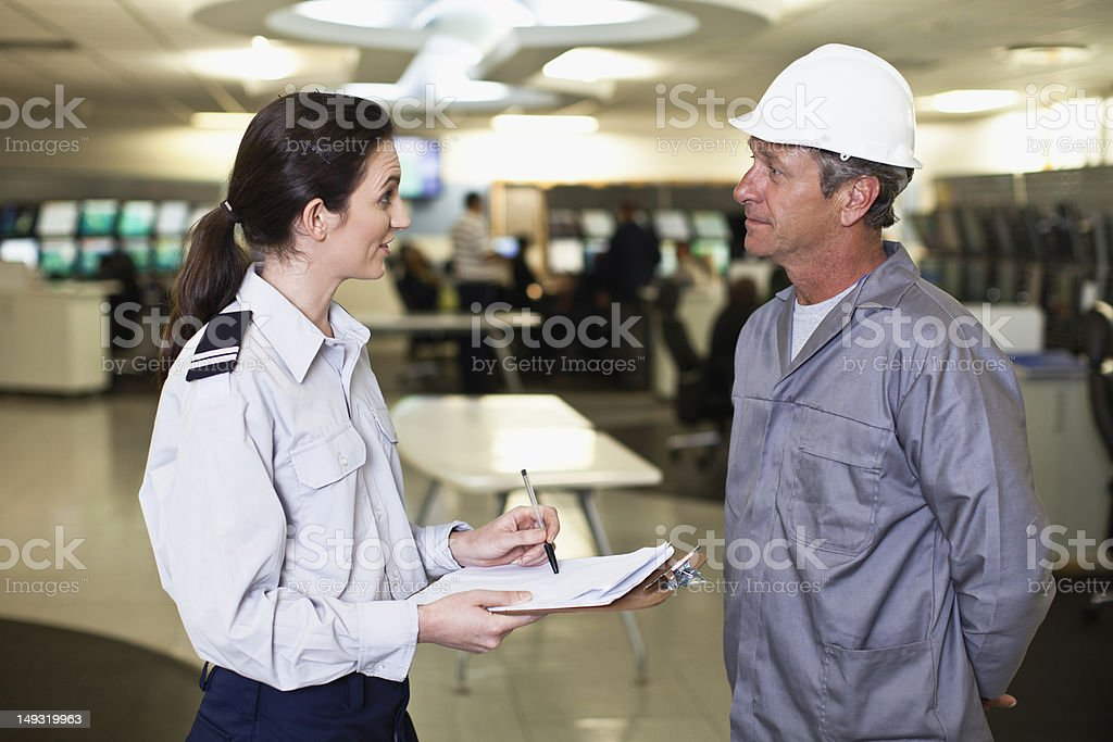 Security personnel talking to worker