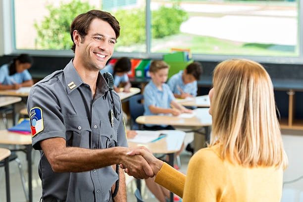 Security professional greets school teacher in classroom Happy security officer shakes hands with elementary school teacher. Students are working in the background. police meeting stock pictures, royalty-free photos & images