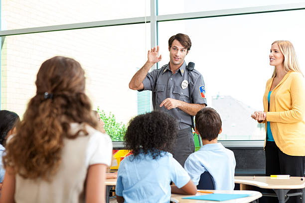 Security professional talks with group of school children Policeman gestures while talking to a group of kids in their classroom. The students are learning about safety. The students' teacher is standing with the officer in front of the class. police meeting stock pictures, royalty-free photos & images