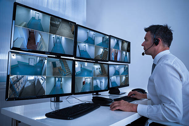 Security System Operator Looking At CCTV Footage At Desk Rear view of security system operator looking at CCTV footage at desk in office security stock pictures, royalty-free photos & images