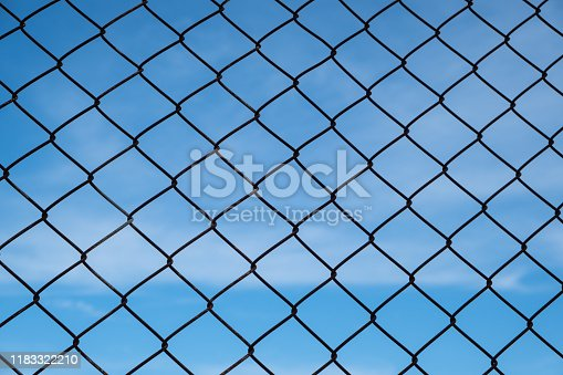 Security with a barbed wire fence in foreground and blue sky in background