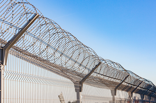 istock Security with a barbed wire fence 995010696