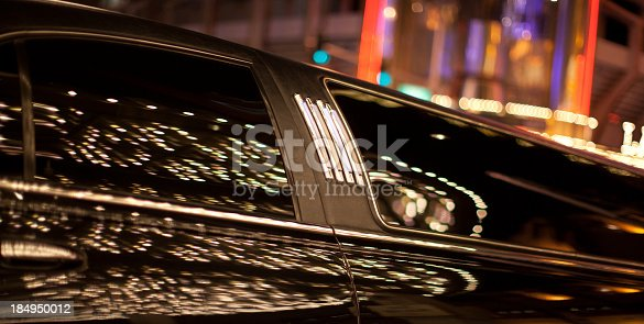 Lights reflecting on a black limousine parked outside a casino.