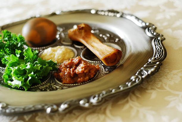A Seder plate at Passover on a tablecloth Traditional symbols on a seder plate for the Jewish festival of Passover.  seder plate stock pictures, royalty-free photos & images