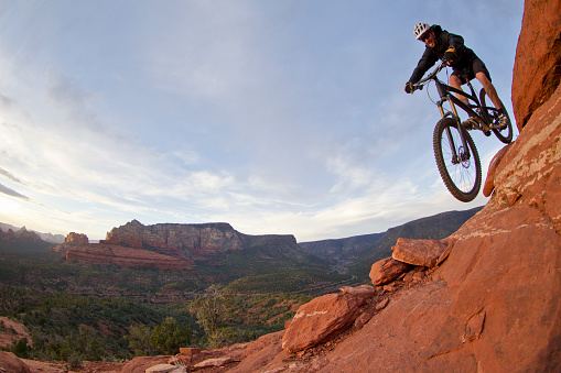 A male mountain biker rides down the Hangover Trail near Sedona, Arizona, USA. The Hangover Trail is an expert level ride and is characterized by a series of rock formations that mountain bikers ride around and underneath then a steep downhill at the finish.