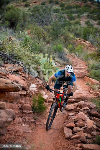 A man rides down a popular trail in Sedona, Arizona, USA. He is riding an enduro-style mountain bike and wearing a bicycle helmet.