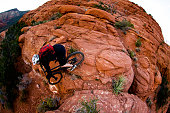 A male cyclist rides a steep mountain bike trail in Sedona, Arizona, USA.