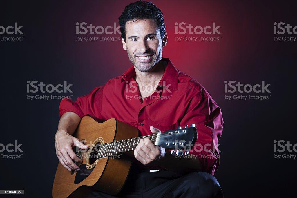 Seducting handsome man serenading with guitar royalty-free stock photo