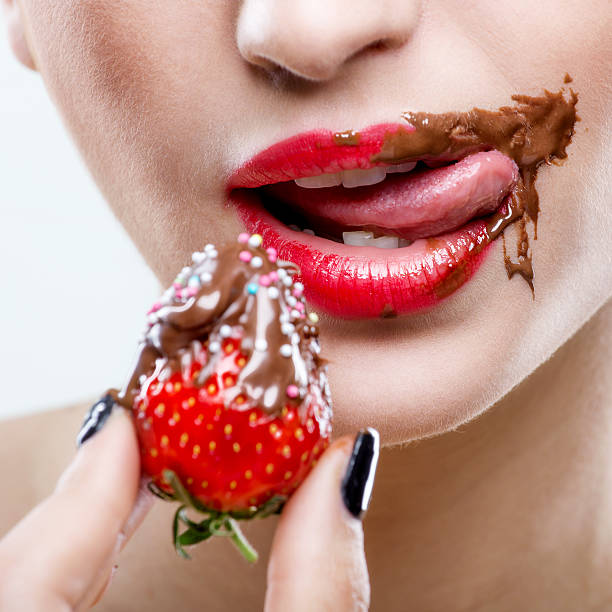 Seduction - red female lips with chocolate mouth , holding strawberries stock photo
