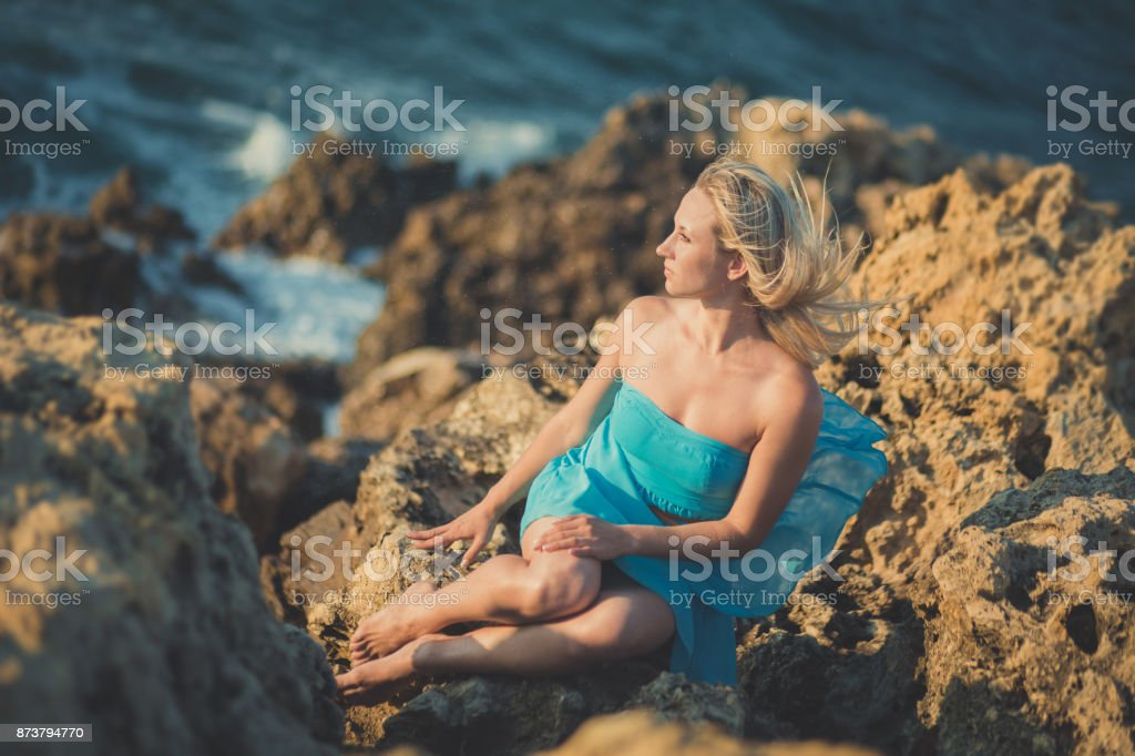 Seductive blond lady woman with sexy naked legs shoulders and arms wearing light blue open dress posing enjoying vacation time on sea side ocean beach alone lonely. stock photo