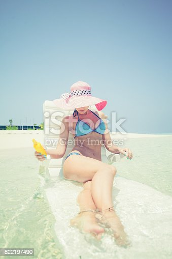 istock Seductive blonde woman sitting and sunbathing in shallow water, Maldives 822197490