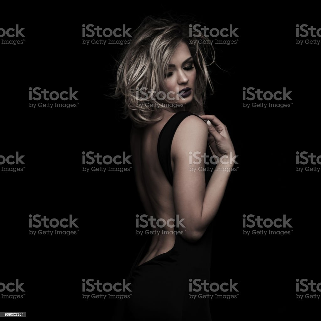 seductive elegant woman with messy blonde hair looking down stock photo