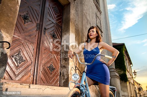 Seductive pin up girl on retro bicycle posing in sunset in old town