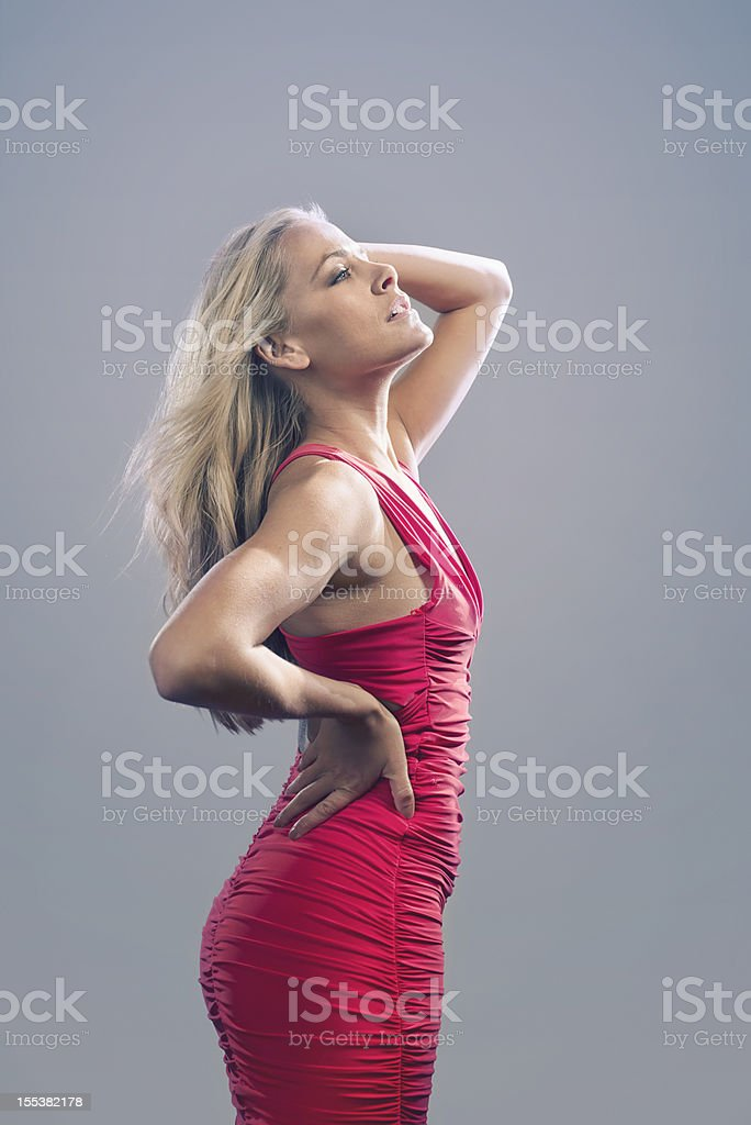 Seductive woman in tight pink dress with hands in hair. royalty-free stock photo