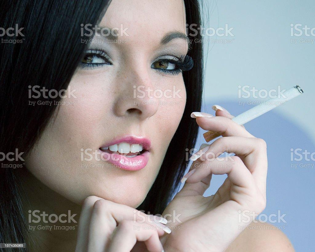 Seductive woman smoking cigarette stock photo