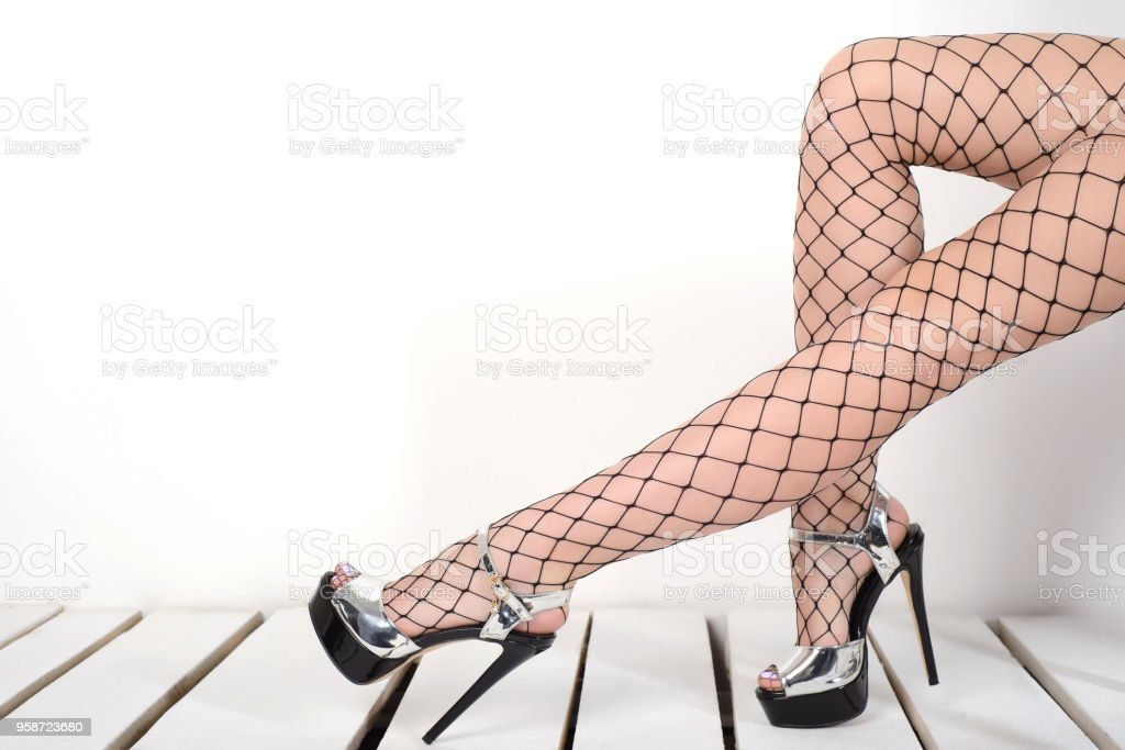 b002b3ac37b0 Seductive woman s legs wearing fishnet stockings and high heels silver  shoes royalty-free stock photo