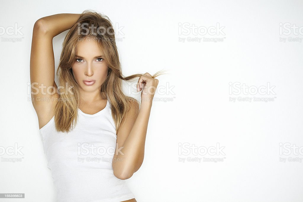 Seductive, young, beautiful, blonde woman leaning against a white wall stock photo