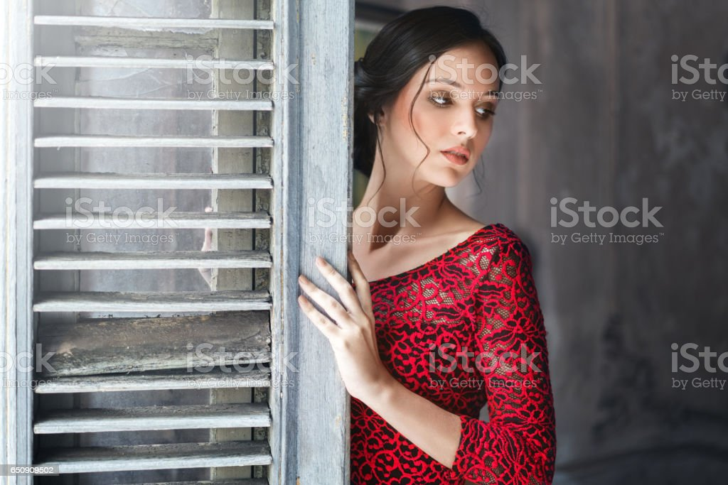 Seductive young woman leaning on door at home stock photo