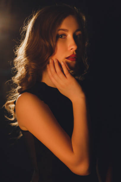 Seductive young woman posing on a black isolated background stock photo