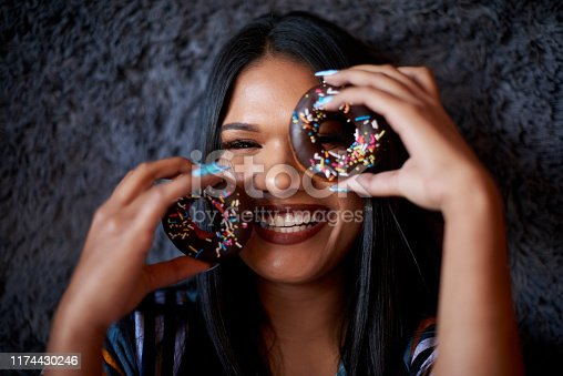 Portrait of an attractive young woman holding up doughnuts and looking through their holes against a dark background